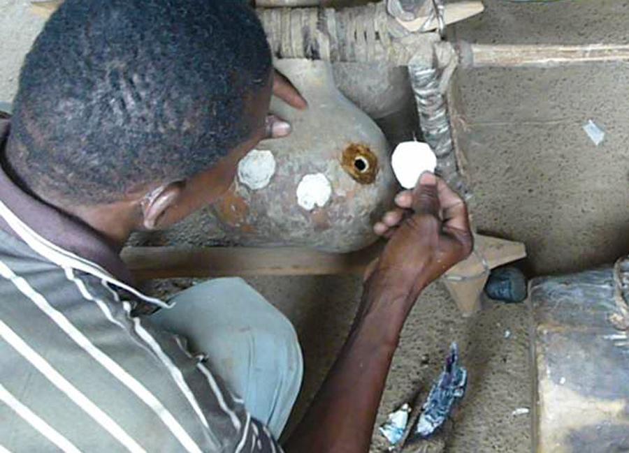 Vuur Sandaar applying a mirliton to a kogyil in his workshop in Donyɛ.